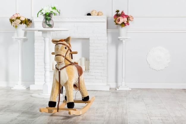 Деревянная игрушка лошадка-качалка стоит декоративный камин и голубая стена и подставки с цветами