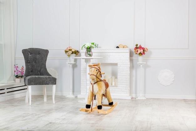 Деревянная игрушка лошадка-качалка стоит возле декоративного камина и светлого настенного серого кресла возле него