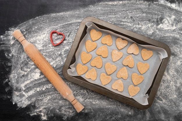나무 롤링 핀과 베이킹 시트와 하트 모양의 쿠키