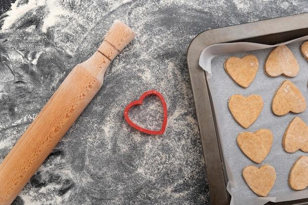木製の麺棒とハート型のクッキーが付いた天板
