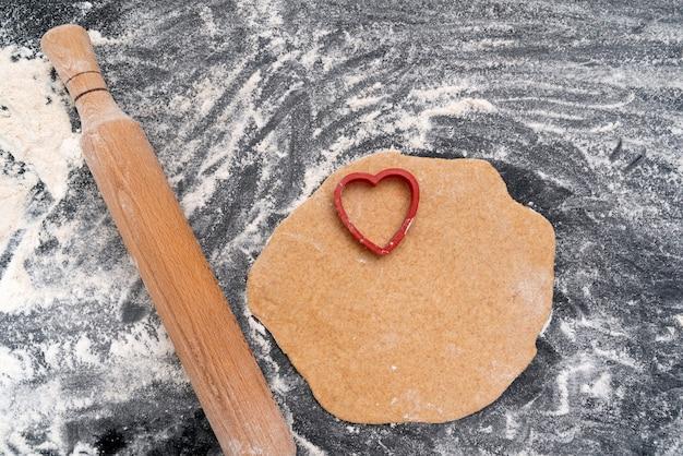 ハート型のプリントが施された木製の麺棒と生地