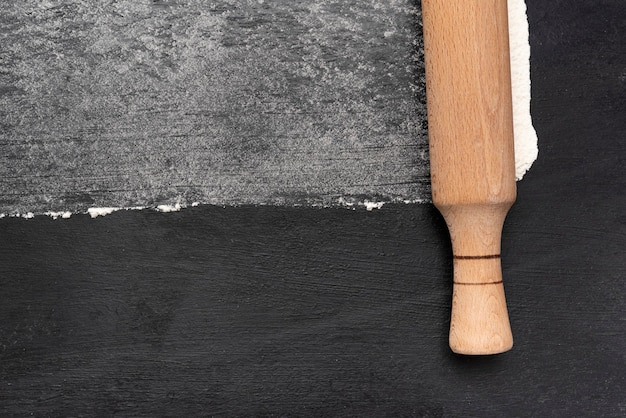 黒の背景の上面図に木製の麺棒と小麦粉。