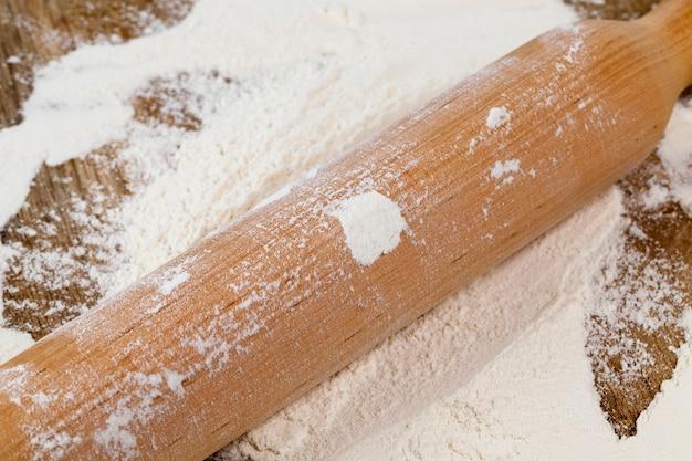 Деревянная скалка в муке во время приготовления