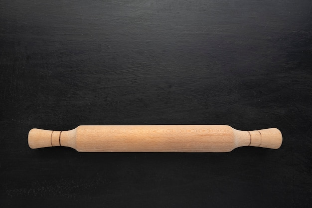 黒の背景、上面図に木製麺棒。コピースペース、キッチンコンセプト。