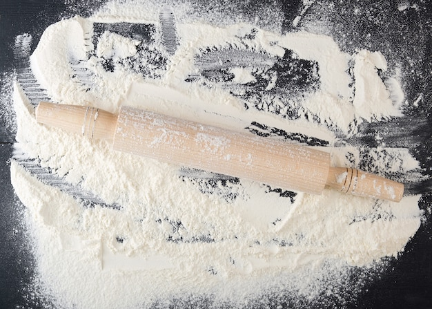 Wooden rolling pin and white wheat flour scattered on a black surface