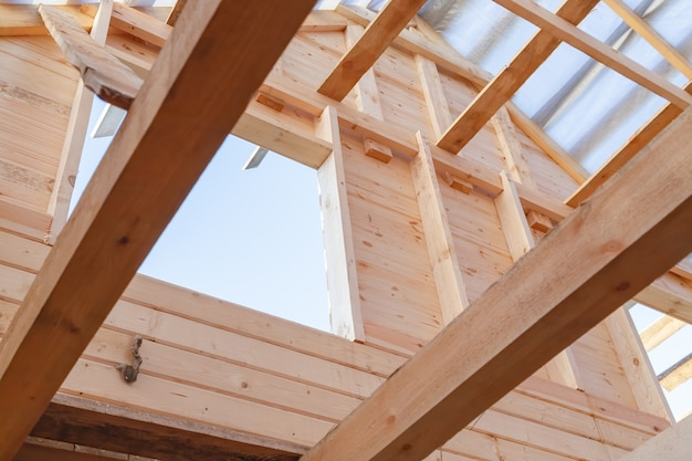 Деревянный каркас крыши и стена из бруса домостроение