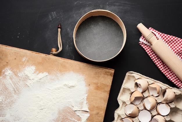 木製の丸いふるい、白い小麦粉、トレイに鶏の卵のトレイ、黒いテーブルに麺棒
