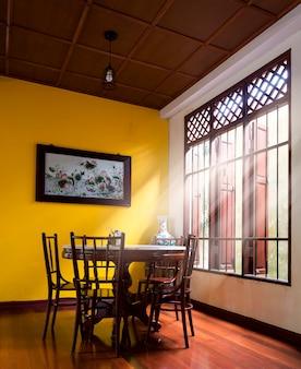 Деревянный круглый стол и стул в стиле chiness возле окна имеют луч света на деревянном полу, а на желтой стене есть изображение лотоса.