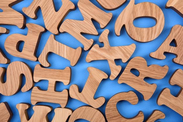 青い背景に木製の丸い文字がランダムに散らばっています。