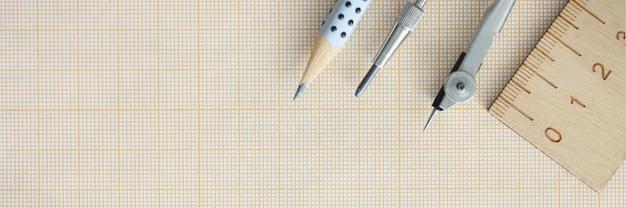 木製の定規のコンパスと鉛筆は方眼紙の上にあります