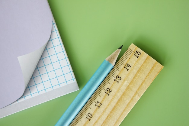Wooden ruler and pencil are near the school notebook on a green background.