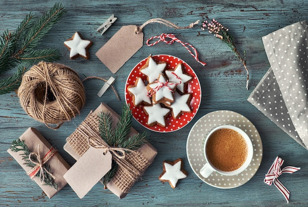 Wooden rustic background with cup of coffee and wrapping of christmas cookies, space