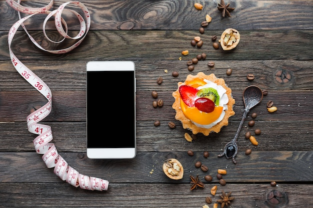 Wooden rustic background with fruit tart and peanuts, coffee beans, walnuts. tasty dessert with whipped cream.