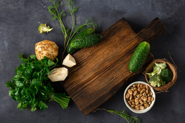 Wooden rustic cutting board with ingredients for cooking vegan food on dark background top view