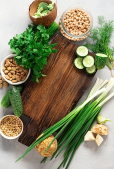 Wooden rustic cutting board with ingredients for cooking vegan food on light background top view