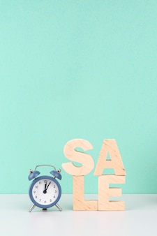 Wooden sale lettering next to clock on blue background