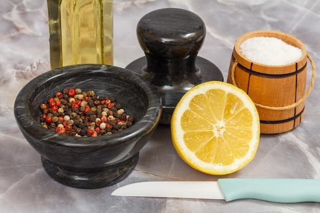 회색 배경에 후추가 든 나무 소금 저장고와 돌 그릇.