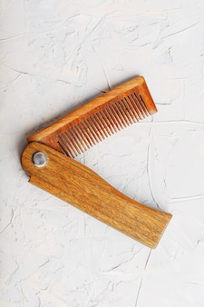 Wooden sandalwood comb folding on a white textured wall.