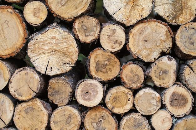 ラックに1対1で積み上げられた木製の製材された丸太。 Premium写真