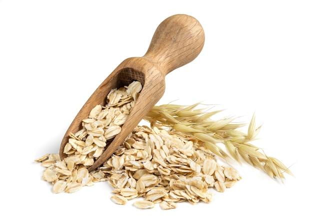 白で隔離されたオーツ麦植物の束と木製のスクープとオーツ麦フレーク。