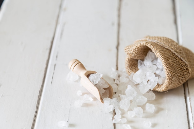 Wooden scoop of crystalline sugar and sugar bag on white wooden floor