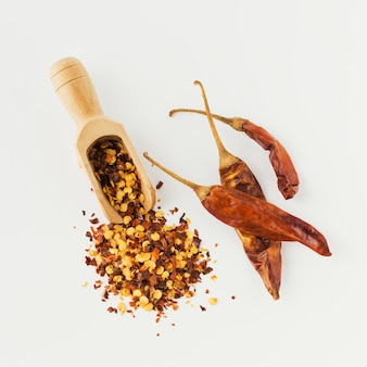 Wooden scoop full of crushed red cayenne pepper, dried chili flakes and seeds