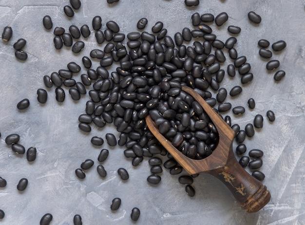 灰色のテーブルトップビューに乾燥黒豆でいっぱいの木製スクープ。健康的な食事と菜食主義の概念。伝統的なラテンアメリカのいとこ成分