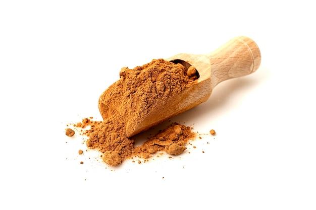 Деревянный совок с рожковым маслом какао-порошка на белом фоне