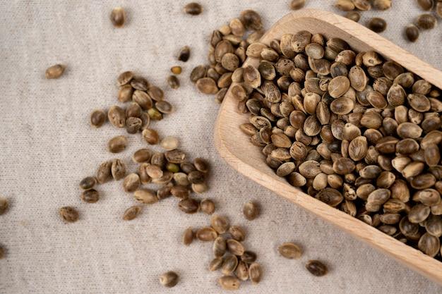 Деревянный совок с семенами конопли на текстильном материале из конопли на столе с деревянной ложкой с семенами конопли