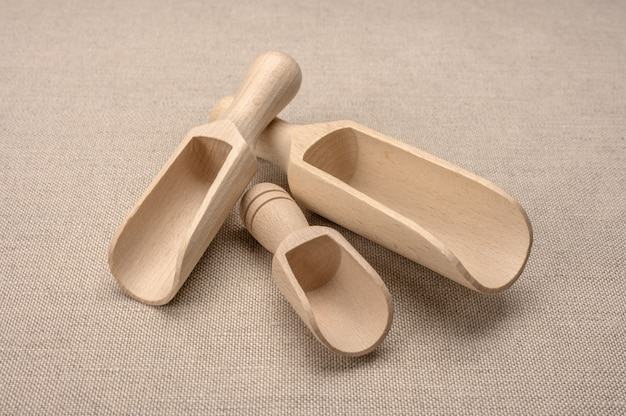 Ковши деревянные для сыпучих продуктов. новый деревянный ковш для сыпучих продуктов и специй на фоне вретища