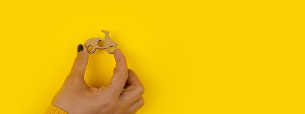 노란색 배경, 빠른 배달 개념, 파노라마 모형 위에 손에 나무 스쿠터