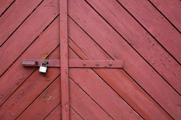 金属ロック付きの木製の傷のあるゲート。テキスト用のスペース