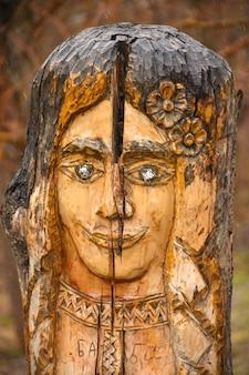 여자 얼굴 모양의 공원에 있는 나무 조각, 갈색 나무 조각
