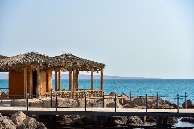 海と山々を背景にした木製の桟橋。
