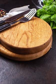 木製のサービングボードとカトラリーフォークとナイフゼロウェイストミールをテーブルにコピースペースフード
