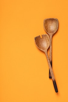 Wooden serving spoons on colorful background
