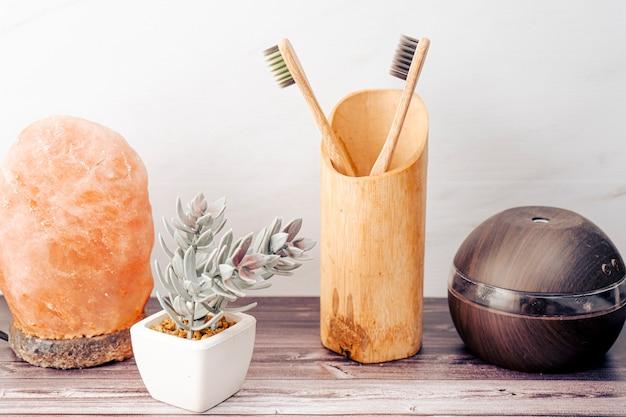 加湿器と有機歯ブラシ付きソルトランプ付きのバスルームの木製棚