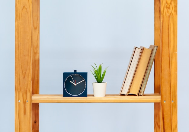 Wooden shelf with alarm clock and objects against blue background