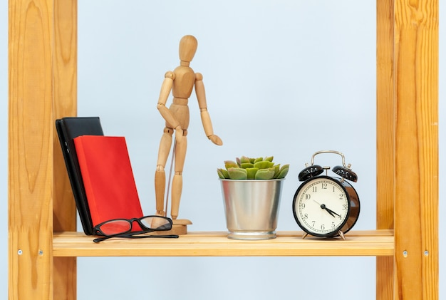 Wooden shelf with alarm clock and objects against blue