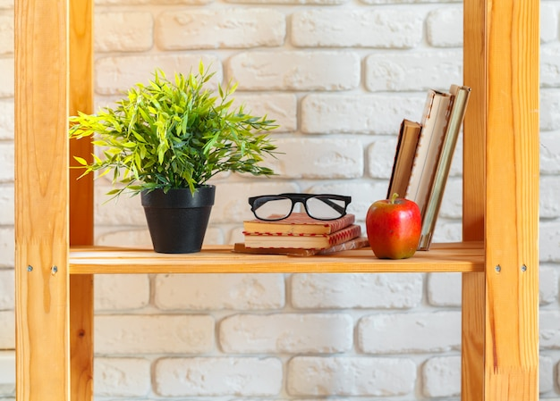 Wooden shelf with home decor with plants