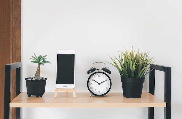 携帯電話、鍋の草、花瓶の緑、アラーム、自宅のリビングルームの白い壁の装飾上のブラックボードと木製の棚
