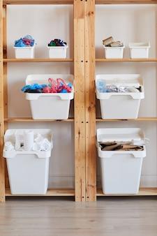 自宅でごみを分別するためのプラスチック製のゴミ箱が付いた木製の棚ラック