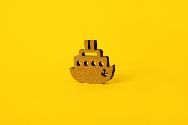 黄色の背景、旅行または夏休みの概念上の木製の船のシンボル