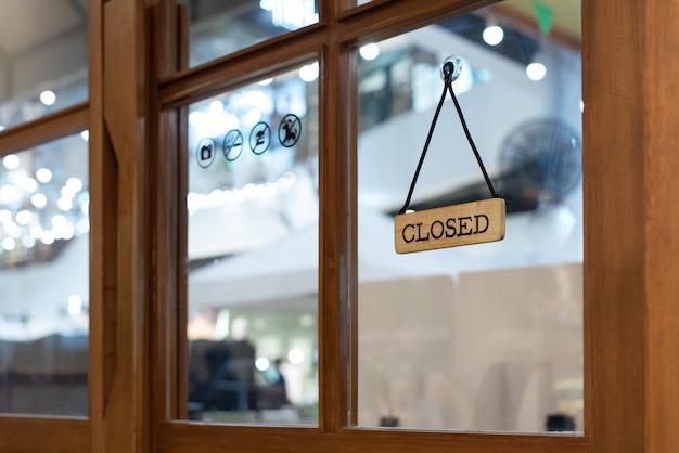 Wooden shop closing sign hang at the shop door