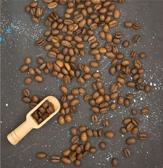 Wooden shovel among scattered roasted coffee beans on a dark background with white patches top view