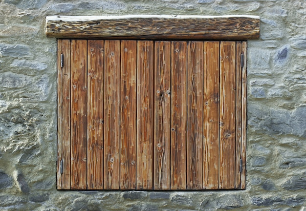 Wooden shutters closed on a stone facade of a mountain chalet