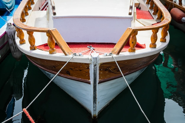 Wooden side of the boat, painted white and brown, with a beautiful wooden fence and ropes against the background of sea water