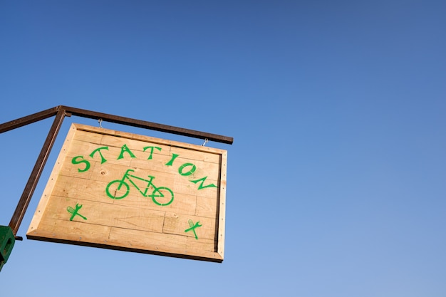 Wooden sign of a bicycle parking station, isolated against blue sky background.