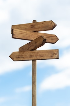 Wooden sign post isolated on blue sky with white clouds