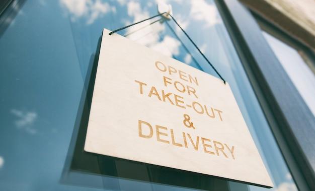 Деревянный знак с открытой для вывоза и доставки, висящий на двери